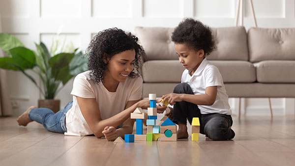 mum and child building home from toy bricks