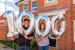 Karla Wilson and Jeremy Atkin-Smith outside their new Milton Keynes home with 1,000th resident balloons