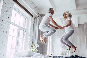 Older Persons Shared Ownership - couple jumping for joy on a bed