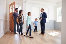 Estate agents showing a family around a new home